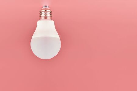 Light bulb, copy space. Energy saving minimal idea concept.Pink background.