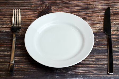 Empty plate on table with cutlery. Visitor of an luxury restaurant is waiting for an order. Restaurant business went broke concept