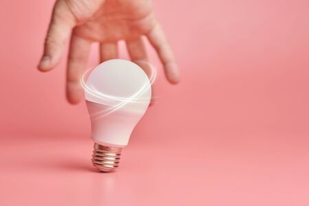 Light bulb and hand, idea catching concept. Symbol of new events or finding solutions to problems. Creative minimal innovations.