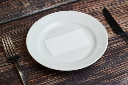 Empty plate on table with cutlery and blank business card, top view. Message for visitor of restaurant or cafe. Business lunch without tips concept.