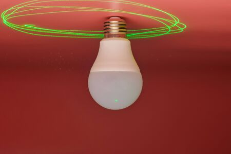 Light bulb and green laser beam around, energy saving. Minimal idea concept.