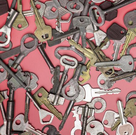 Keys set on pink background. Door lock keys and safes for property security and house protection. Banque d'images