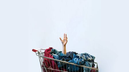 Female hand sticks out of shopping cart full of clothes.