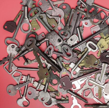 Keys set on pink background. Door lock keys and safes for property security and house protection. Different antique and new types of keys. Foto de archivo