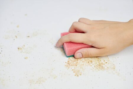 Cleaning kitchen table. Pink sponge in woman hand removes dirt, bread crumbs and leftovers. Household chores Archivio Fotografico