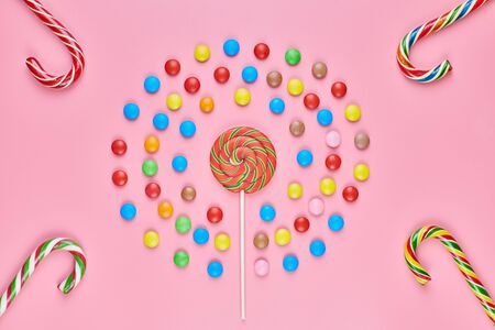 Sweet lollipops and candy canes on pink background, copy space. Love to colorful sweetmeats in childhood concept Imagens
