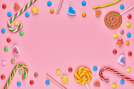 Sweet candy copy space frame with lollipops on pink background. Love to colorful sweetmeats in childhood concept