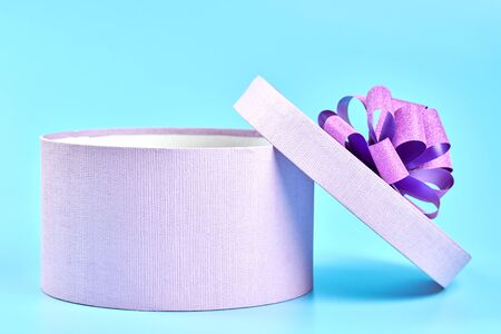 Round gift box with bow. Purple opened box for gift on blue background. Package for surprise for any holiday: Birthday, Valentines day, Christmas, Anniversary, Wedding and other celebration