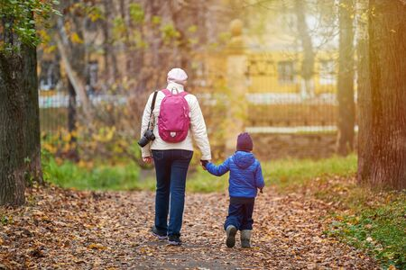 Mother or nanny and little boy walking together in autumn city park, back view. Girl holds boys hand. Single parent, divorce or widow concept. Zdjęcie Seryjne