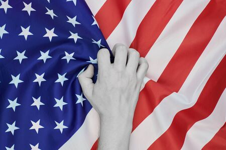 Colorless hand crumpled national USA american flag. Racism and white american discrimination concept. Stock Photo