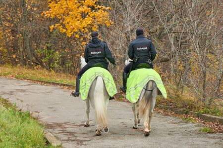 Mounted police in autumn city park, back view. Two russian police officers on horseback patrol the park. POLICE inscription on the back.