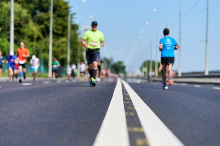 Runners on city road. Running marathon, copy space. Street sprinting outdoor competition. Healthy lifestyle, fitness sport event. Stockfoto