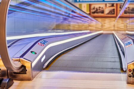 Moving walkway in shopping center. Horizontal slow-moving conveyor mechanism for easy elevation. Travelator to food store for disabled people on wheelchair.