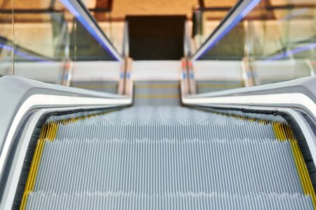 Escalator in shopping center. Close up escalators stairs up and down in office building, shopping mall or subway station.