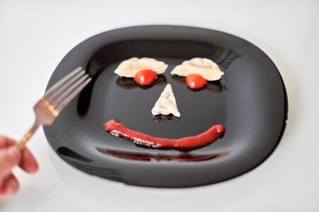Food face, funny dumpling and ketchup. Smiling face on plate. Food art on black plate. Motivation for losing weight and healthy eating.