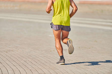 Running man. Athletic man jogging in sportswear on city road. Healthy lifestyle, fitness sport hobby. Street workout, sprinting outdoor