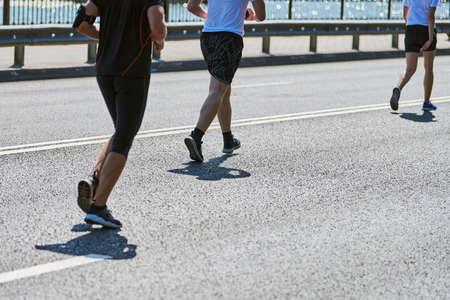 Running man. Athletic man jogging in sportswear on city road. Street marathon race, sprinting outdoor. Healthy lifestyle, fitness sport hobby.