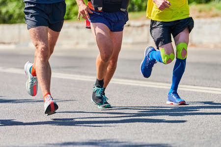 Running men. Sport men jogging in sportswear on city road. Healthy lifestyle, fitness hobby. Street marathon race sprinting outdoor Imagens