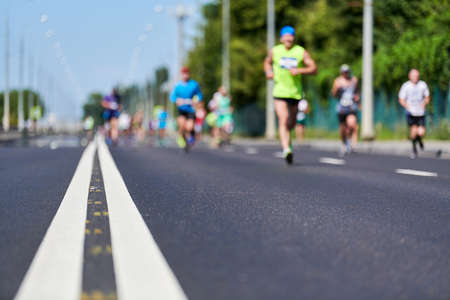 Marathon runners on city road. Running competition, copy space. Street sprinting outdoors. Healthy sport event.