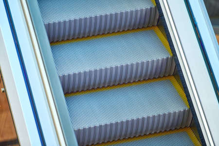 Escalators in shopping center. Empty moving staircase up and down in office building, shopping mall or subway station.