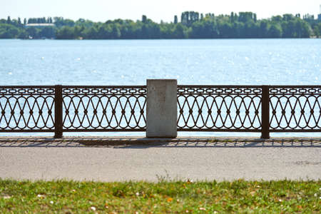 Iron fencing on waterfront. Riverside decor fence. Outdoor urban pathway for walking with enclosure