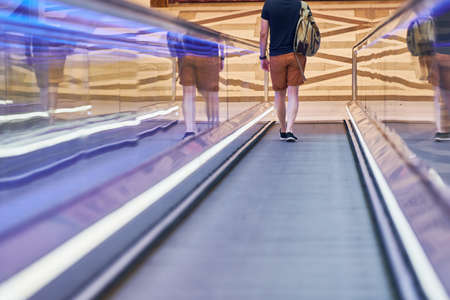 Young man goes down on moving walkway in shopping center. Horizontal slow-moving conveyor mechanism for easy elevation. Travelator for easy moving to food store. Editorial