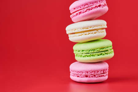 Macaroons on red background. Colorful small cookie from ground almonds and coconut. Popular confectionery. Tasty snack food for take away, copy space