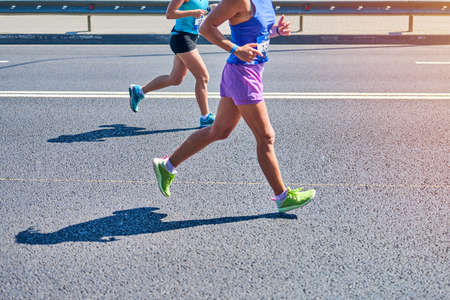 Running women. Sport women jogging in sportswear on city road. Healthy lifestyle, fitness hobby. Street marathon race, sprinting outdoor