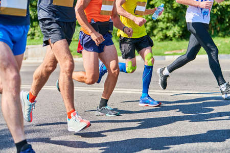 Marathon runners on city road. Running competition. Street sprinting outdoor. Healthy lifestyle, fitness sport event. Stock Photo