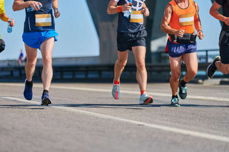 Marathon runners on city road. Running competition. Street sprinting outdoor. Healthy lifestyle, fitness sport event.