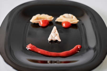 Food face, funny dumpling and ketchup. Smiling face on plate. Food art on black plate. Motivation for losing weight and healthy eating. Banque d'images