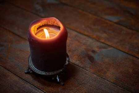 Big candle on wooden table. Burning candle in a candlestick, vintage gothic style, copy space. Design for magic ritual and predictions