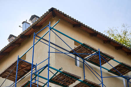 Scaffolding on construction site. Incomplete building and decoration with scaffolds. Work in progress on new apartment block