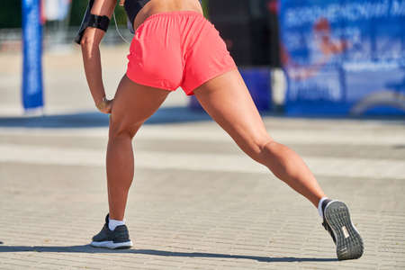 Young woman warming up before running marathon. Beautiful girl with tan legs. Outdoor fitness stretching exercise. Sport party.