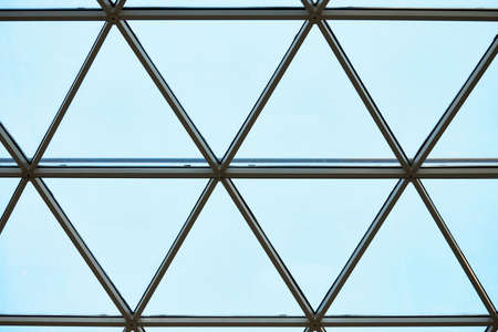 Transparent ceiling in business center. Glass triangle windows. Mesh structure architecture. Abstract geometric pattern of framed glass