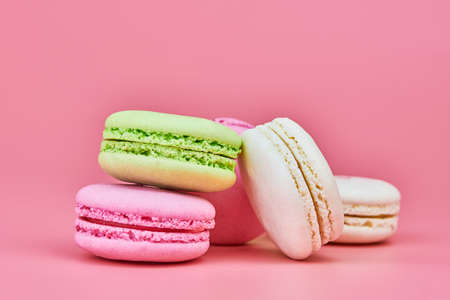 Macaroons on pink background. Colorful small cookie from ground almonds and coconut. Popular confectionery. Tasty snack food for take away, copy space