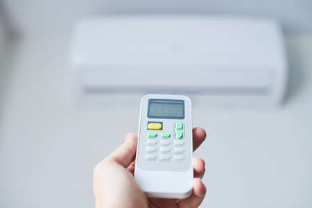 Remote control for air conditioner in hand. Room condition remote control. Air temperature switch for cooling of space. Stock Photo