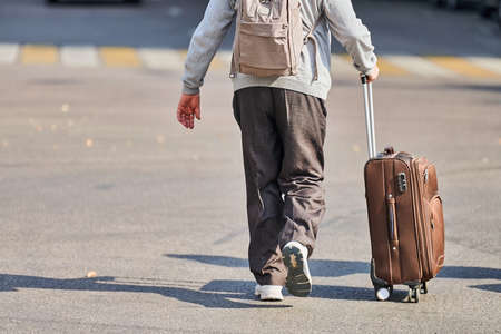 Old man with suitcase on wheels. Male with luggage bag walking down the street from airport. Homecoming after travel trip. Jet lag effect. Back view