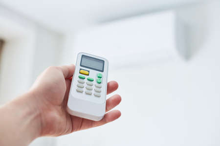 Air condition remote control. Hand with room conditioner remote control. Air temperature switch for cooling of space.
