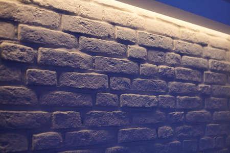 Brick wall indigo lighting. White wall blue glow in modern vintage loft interior. Unusual room design in evening light