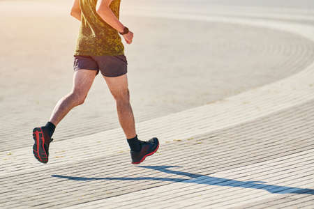 Running man. Athletic man jogging in sportswear on city road. Healthy lifestyle, fitness sport hobby. Street workout, sprinting outdoor Banco de Imagens