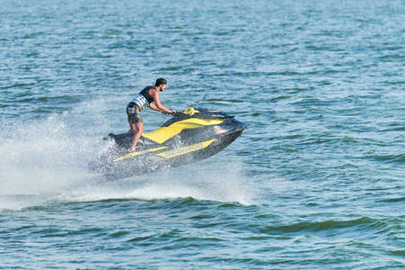 Voronezh, Russia - 23.08.2019 - Man on water scooter. Summer vacation on personal watercraft in tropical sea. Young guy sea riding hobby. PWC sport activity