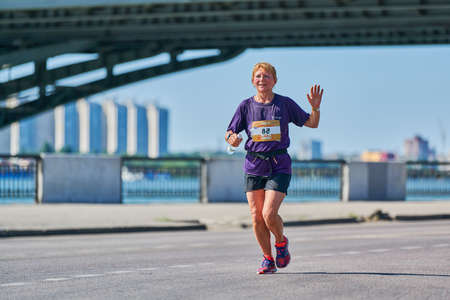 Voronezh, Russia - 08.24.2019 - Young girl runs along road. Runners marathon and championship competition, copy space. Street sprinting outdoors. Healthy sport event.