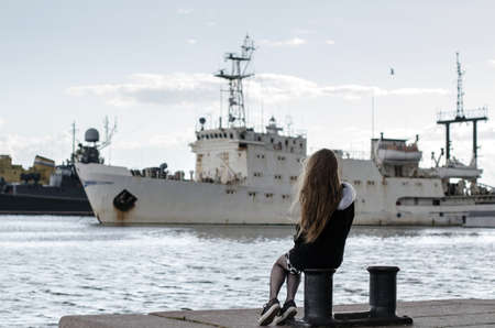 Young girl back view looking at ships. Woman dreaming about sea travel. Long-haired female sitting on moorings, ships in port background. Loneliness concept