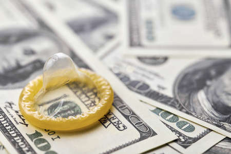 Condom and US dollars. Prostitution concept. Pay for per night. Harlotry and whoredom. US dollar money on table with contraceptive.