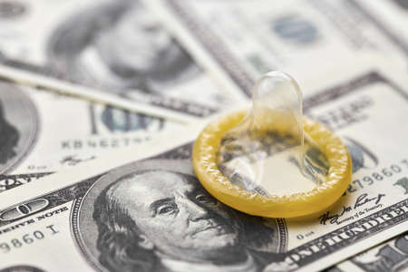 Condom and US dollars. Prostitution concept. Pay for per night. Harlotry and whoredom. US dollar money on table with contraceptive. Standard-Bild