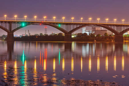Night city bridge lighting. Beautiful reflection of night lights on water surface. Long exposure photography.