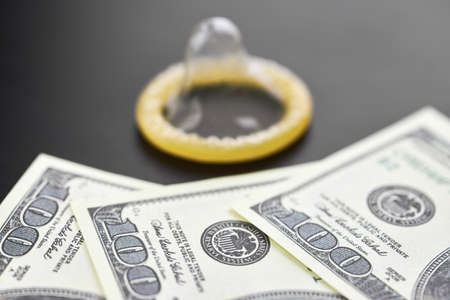 Condom on dollars bills. Prostitution concept. US dollar money on table with contraceptive. Pay for per night. Harlotry and whoredom.