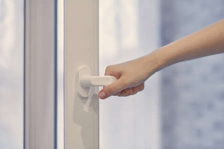 Woman holding white modern handle at PVC plastic window with double glazing, opening and closing frame. Close up. Imagens