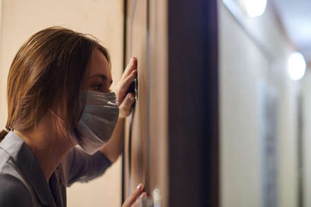 Young woman in medical mask looking through peephole of front door in apartment when somebody rings doorbell. Stay home and self isolation concept. Home quarantine, prevention of COVID-19.